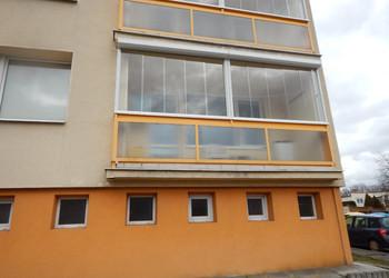 Realizace bezrámového posuvného zasklení balkónů v bytovém domě se zastíněním předokenní roletou s větracími lamelami
